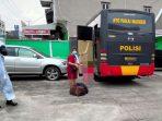 Seorang pasien isoman saat dijemput dan dipindahkan ke tempat isolasi pemerintah oleh pihak kepolisian